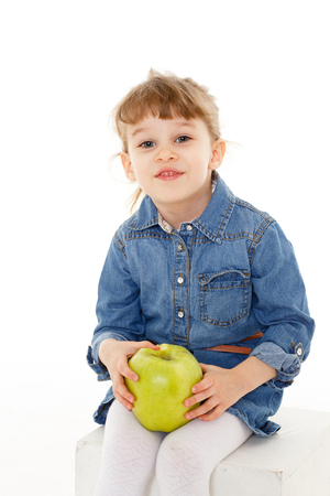 3 year old: Sweet small girl with fresh big an apple sits on a white background. Healthy food. 3 year old.