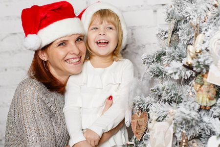 decorating christmas tree: The pretty girl with mum are decorating a Christmas tree in the house. Happy family.