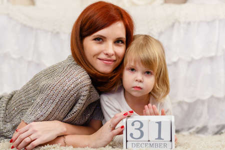 Happy mother and sweet little daughter with date 31 december are lying on the carpet in the room . Eve of New Year. photo