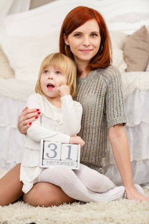 Happy mother and sweet little daughter with date 31 december are sitting on the carpet in the room . Eve of New Year. photo