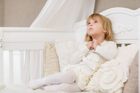 resentful: Resentful pretty little girl sits on a sofa in the room.