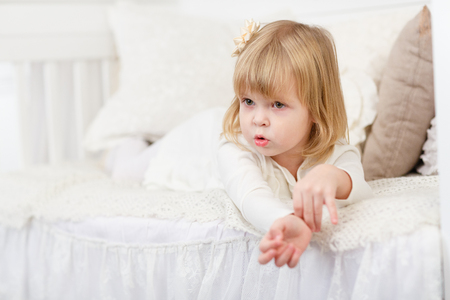 one child: Resentful pretty little girl lies on a sofa in the room.