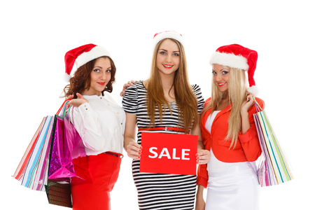 christmas shopping bag: Three pretty young women in Santas hat with shopping bags stand on a white background. Christmas sale.