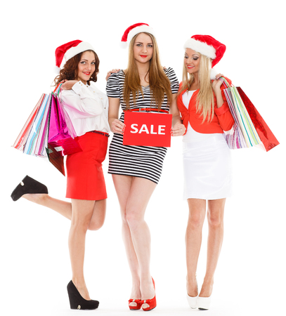 Three pretty young women in Santa's hat with shopping bags stand on a white background. Christmas sale. photo