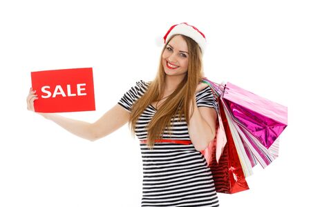 Pretty young woman in Santa's hat with shopping bags stands on a white background. Christmas sale. photo