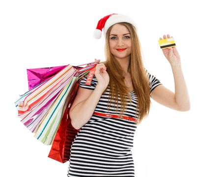 Pretty young woman in Santa's hat with shopping bags and credit card  stands on a white background. Christmas sale. photo