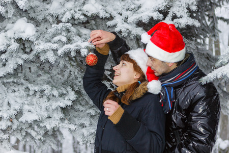 woman hanging toy: Young couple in a Christmas cap decorate a fur-tree in winter wood.