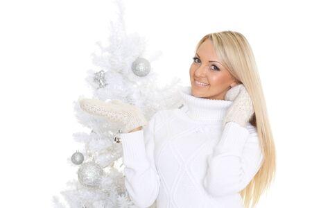femme chatain: Jeune femme heureuse dans les vêtements d'hiver se tient près de l'arbre de Noël sur un fond blanc et est titulaire d'un objet imaginaire dans une main. Espace libre pour la publicité de votre produit.