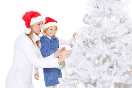 woman hanging toy: The pretty girl with mum decorate a Christmas tree on a white background. Happy family. Stock Photo