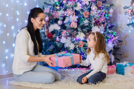 young tree: Happy family with  gifts sitting near Christmas tree at home. Merry Christmas and New Year. Stock Photo