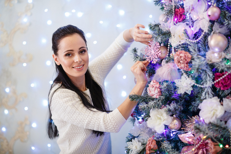 decorating christmas tree: Beautiful young woman is decorating a Christmas tree in the house. Merry Christmas and New Year.