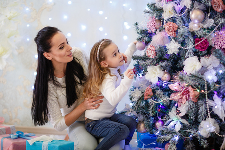 decorating christmas tree: The pretty girl with mum are decorating a Christmas tree in the house. Happy family. Merry Christmas and New Year. Stock Photo
