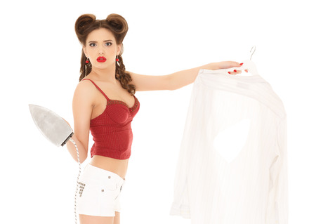 discomfiture: Young unhappy beautiful woman with shirt and iron on a white background. Housekeeping.