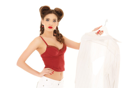 discomfiture: Young unhappy beautiful woman with spoilt shirt on a white background. Housewife.