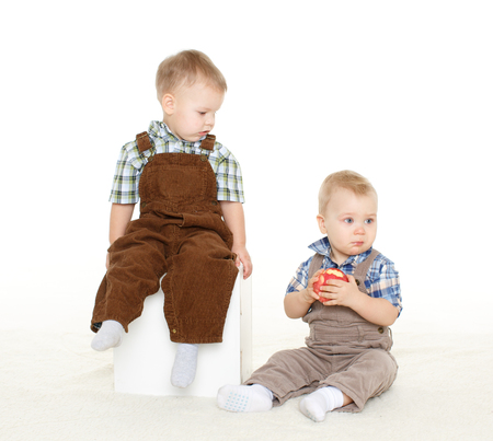 sibling rivalry: Two little boys with fresh apple sit on a white background. Healthy food.