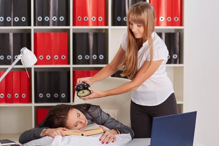 awaking: Young business woman tries to wake the sleeping coworker on a workplace in the office. Overworked.