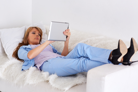 Young business woman with computer tablet lies on the white sofa. photo