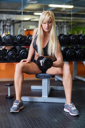 Mujer joven de los deportes que hace ejercicios con pesas de gimnasia en el gimnasio. Aptitud.