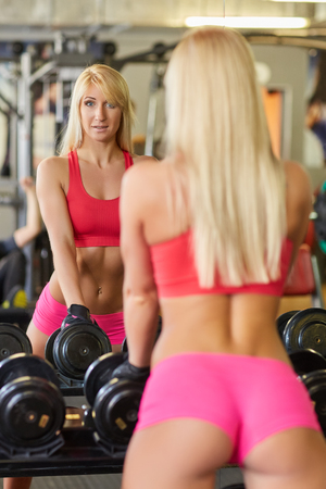 ass standing: Sporty beautiful woman stands in the gym. Fitness.