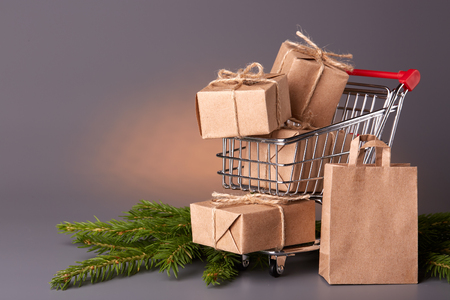 trolly: Shopping trolley with gift boxes and brenches of fir-tree on a grey background. Christmas and New Year sale.