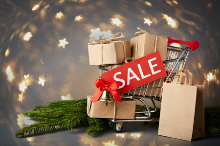 trolly: Shopping trolley with gift boxes, tablet with an inscription sale and brenches of fir-tree on a grey background. Christmas and New Year sale.