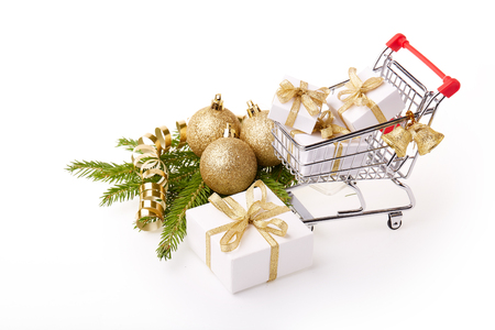 trolly: Shopping trolley with gift boxes and brenches of fir-tree with decoration on a white background. Christmas and New Year sale.