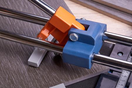 manual measuring instrument: Manual cutter  and ceramic tiles for floor. Home repair.