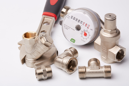 New water meter with fittings and wrench on a white background. Sanitary equipment. Stock Photo