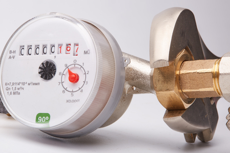 New water meter with fittings and wrench on a white background. Sanitary equipment. Фото со стока