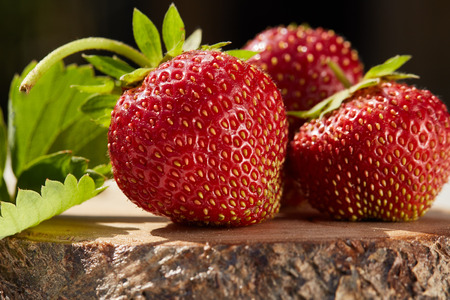 bacca: Fresh strawberries with leaves lies on wooden stump