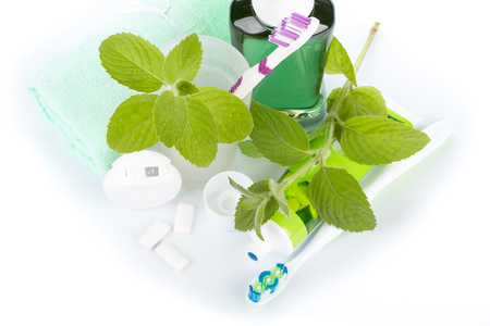 grooming product: Toothbrush with toothpaste and fresh leaves of mint  on a white background.