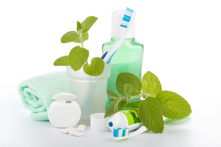 rinsing: Toothbrush with toothpaste and fresh leaves of mint  on a white background.