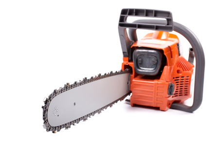 Orange chain saw on a white background. Selective focus on chain.