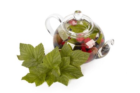 phytotherapy: Teapot with fruit tea and green leaves over white background