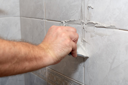 tiling: Male worker tiling a wall.