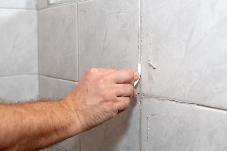 home repairs: The male hand with the rubber stick applies grout on a seam between tiles in a bathroom. Home repairs. Stock Photo