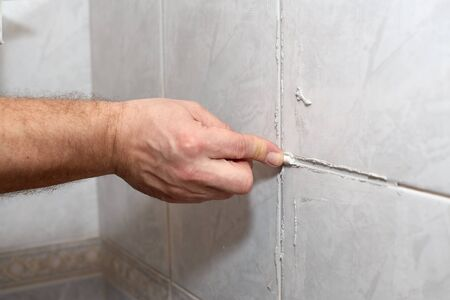 grout: The male hand with the rubber stick applies grout on a seam between tiles in a bathroom. Home repairs. Stock Photo