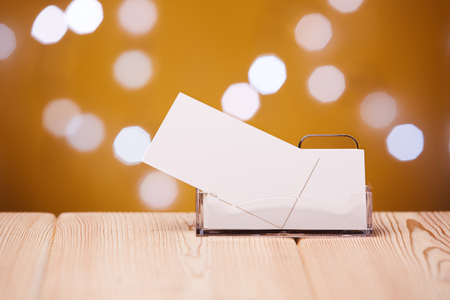Professional blank business cards in holder stands on wooden table on a abstract yellow background.