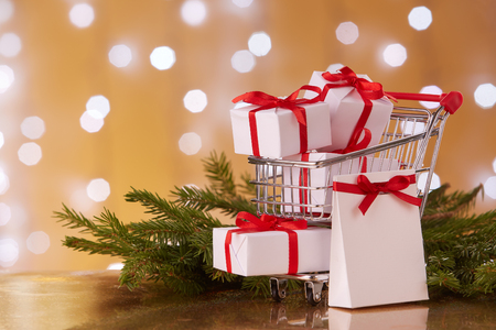 pushcart: Shopping trolley with gift boxes and brenches of fir-tree with decoration on a yellow background with light of garland. Christmas and New Year sale.