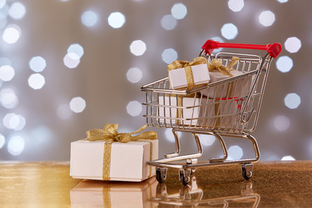 trolly: Shopping trolley with gift boxes and brenches of fir-tree with decoration on a grey background with light of garland. Christmas and New Year sale.
