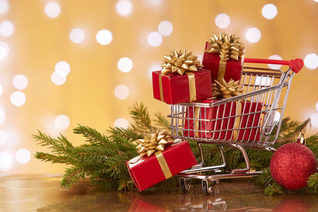 Shopping trolley with gift boxes and brenches of fir-tree with decoration on a yellow background with light of garland. Christmas and New Year sale.