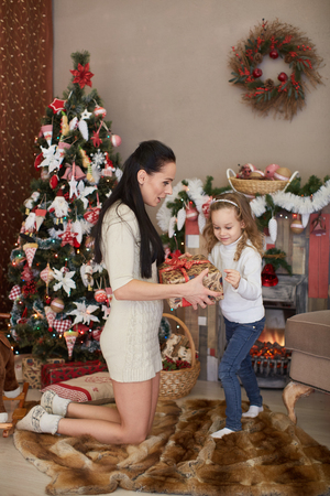 Happy family with  gifts standing near Christmas tree at home. Merry Christmas and New Year. photo