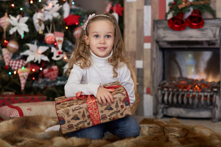 Happy pretty girl with gift box lies near Christmas tree in the room of the house.  Merry Christmas and New Year. photo