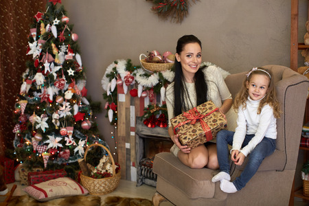 Happy family with  gifts sitting near Christmas tree at home. Merry Christmas and New Year. photo
