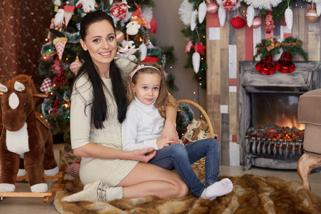 The pretty girl with mum sitting near Christmas tree in the house. Happy family. Merry Christmas and New Year. photo