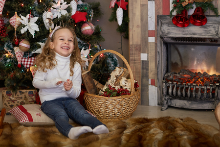 Happy pretty girl sits near Christmas tree in the room. Merry Christmas and New Year. photo