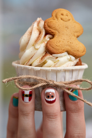 christmas manicure: Female hand with festive  Christmas manicure  holding tasty cupcake. Christmas and New Year treat. Stock Photo