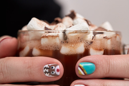 christmas manicure: Female hands with bright festive manicure design holding glass mug with hot cocoa and marshmallows. Winter holidays. Christmas and New Year.