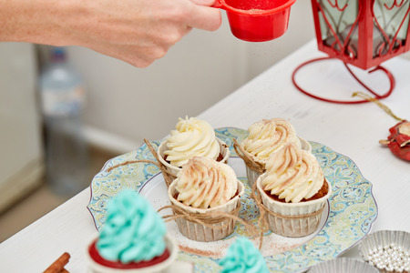 chocolate powder: Christmas Treats. Handmade cookies, cupcakes, confection standing on the table. Female hands decorating cupcakes with chocolate powder. Christmas and New Year. Stock Photo