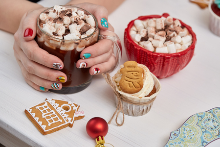 christmas manicure: Female hands with bright festive manicure design holding glass mug with hot cocoa and marshmallows.  Handmade ginger cookies, cupcake,  confection standing on the table. Christmas and New Year treats. Stock Photo